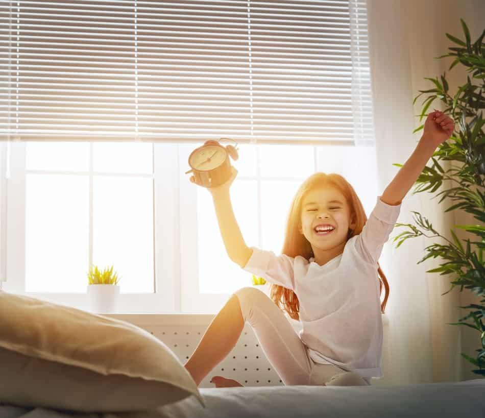 Young girl holding an alarm clock